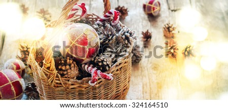Bright Light Spots as Festive effect on Rhoto with Christmas  Fir Tree Toys in Basket, Red balls, Pine cones, Sweet Candy Toys on Wooden background  - stock photo