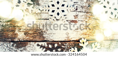 Bright Light with White Wooden Decorative Snowflakes on Old Vintage Background, as the Christmas Decor. Tinted photo - stock photo