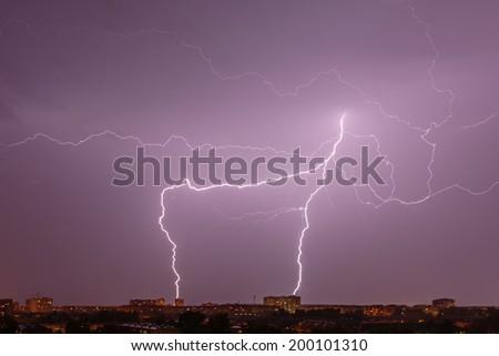 Bright lightning over night city - stock photo
