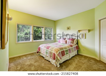 Bright lime bedroom with iron frame bed and colorful bedding