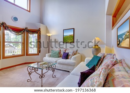 Bright living room. View of corner furnished with white comfortable sofas and antique coffee table with iron legs and glass top