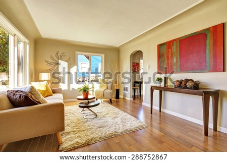 Bright living room with hardwood floor and tan sofa.