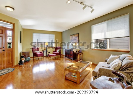 Bright living room with shiny hardwood floor. Furnished with comfortable sofa, coffee table, burgundy antique chairs and cabinet