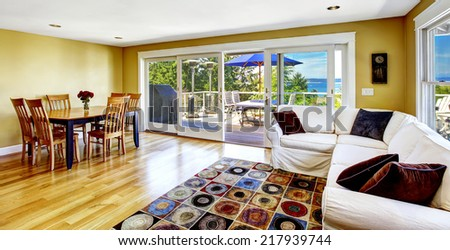 Bright living room with white sofa and dining area. Spacious walkout deck overlooking scenic bay view. Tacoma real estate, WA