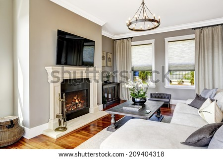 Bright luxury living room with fireplace and tv, white cozy couch and carved wood table with flowers - stock photo
