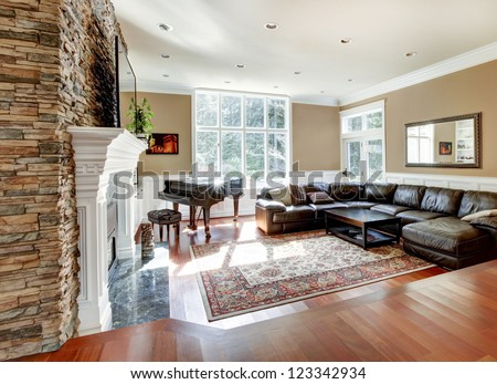 Bright luxury living room with stone fireplace and cherry hardwood with leather sofas. - stock photo