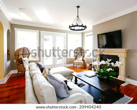Bright luxury living room with walkout deck. Furnished with sofa, black coffee table and antique chairs - stock photo