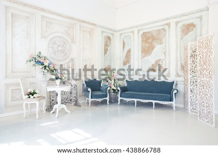 Bright luxury white and blue colored interior living room with flowers in vases. the walls are decorated with baroque ornaments. - stock photo