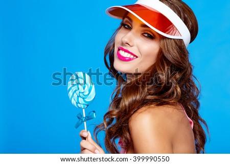 Bright makeup. Beauty Girl Portrait holding Colorful lollipop. Blue background. - stock photo