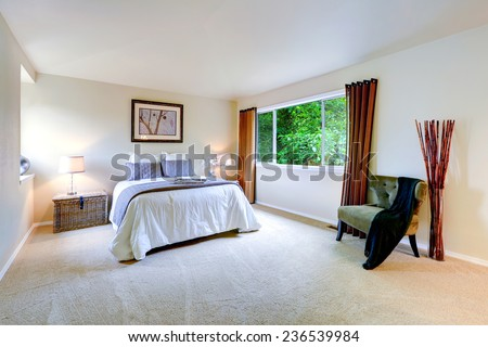 Bright master bedroom interior with brown curtains. Beautiful white bedding with light grey pillows and blanket - stock photo