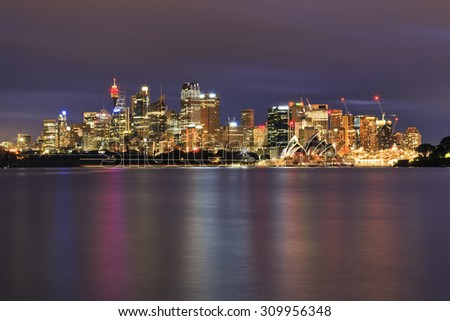 Bright modern cityline of Sydney CBD at sunset in full illumination reflecting in blurred waters of Harbour as viewed from Cremorne point - stock photo