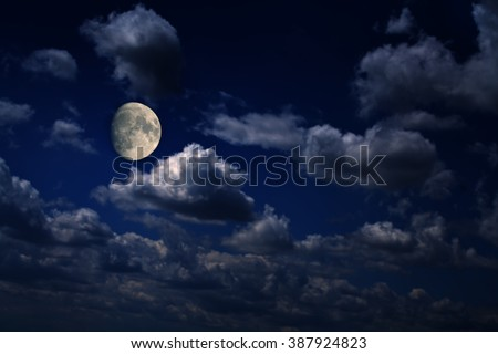 Bright moon over scattered clouds at night