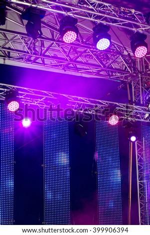 bright multicolored spotlights illuminate outdoor concert stage - stock photo