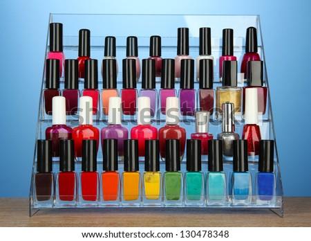 Bright nail polishes on shelf on blue background - stock photo