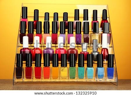 Bright nail polishes on shelf on yellow background - stock photo