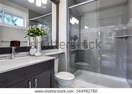 Bright New Bathroom Interior With Glass Walk In Shower With Grey Tile Surround Brown Vanity