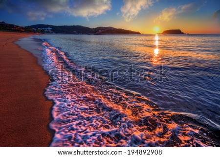 Bright ocean bay sunrise on a sandy beach with a curving shore - stock photo
