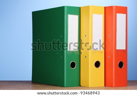 bright office folders on wooden table on blue background - stock photo