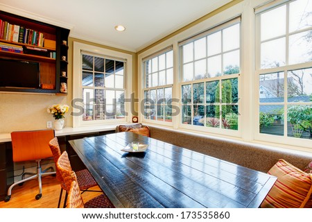 Bright old style kitchen with black dining table, wicker brown chairs and wide windows