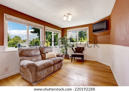 Bright orange and white family room with love seat and tv