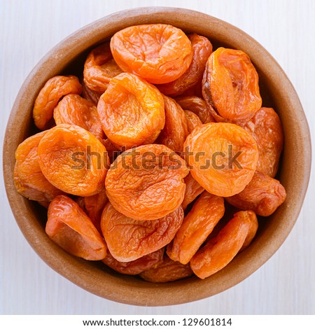 Bright orange apricots in wooden plate on light gray cloth. - stock photo