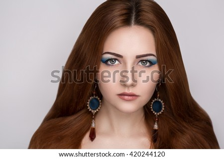 Bright orange brown long straight hair. Oriental beauty girl professional makeup. Portrait of a beautiful woman who wore big earrings accessory. Young gypsy fortune teller predicts fate horoscope - stock photo