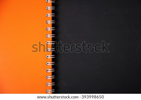 Bright orange colored notebook binder cover on blackboard surface.  Simple and ready to use education background template - stock photo