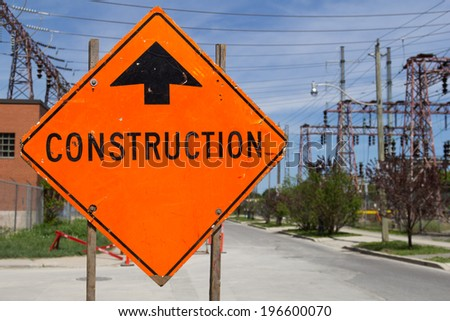 Bright Orange Construction sign by the of a road - stock photo