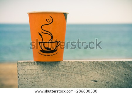 Bright orange disposable cup of coffee standing on a wooden fence against the blue sea. - stock photo