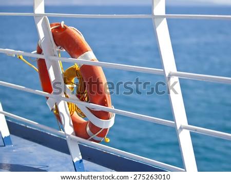 Bright orange lifebuoy on the ferry deck - stock photo