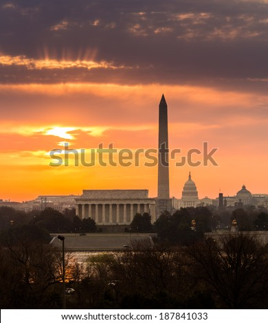 Bright orange sunlight illuminates clouds over Washington DC at dawn at sunrise. Lincoln, Washington Monument and Capitol are aligned