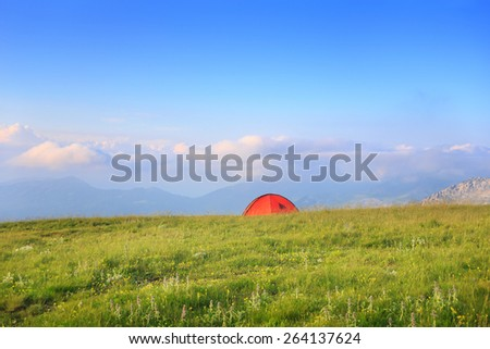 Bright orange tent standing at mountain pasture on green grass with mountain landscape background under cloudy sky - stock photo