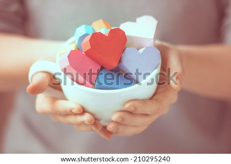 Bright paper hearts in mug in woman hands. Toned picture - stock photo