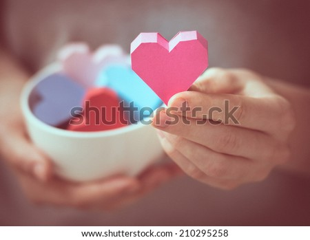 Bright paper hearts in mug in woman hands. Toned picture