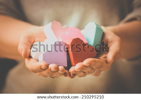 Bright paper hearts in woman hands. Toned picture - stock photo