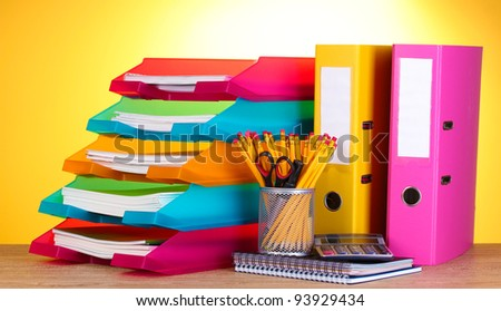 bright paper trays and stationery on wooden table on yellow background - stock photo