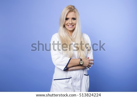 bright picture of an attractive female doctor. Isolated on blue background.