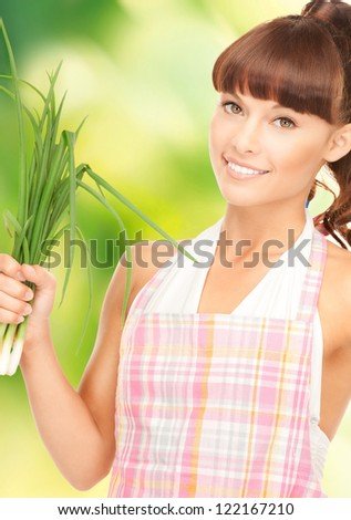 bright picture of beautiful housewife with spring onions over green. - stock photo