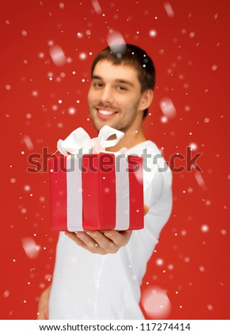 bright picture of handsome man with a gift (focus on box). - stock photo