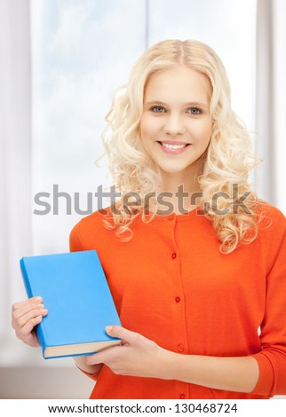 bright picture of happy and smiling woman with book - stock photo