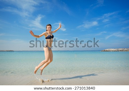 bright picture of happy jumping woman on the beach. - stock photo