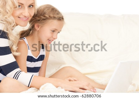 bright picture of happy mother and child with laptop computer (focus on girl)