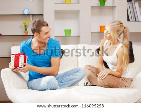 bright picture of happy romantic couple with gift (focus on man)