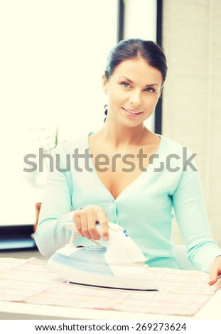 bright picture of lovely housewife ironing clothes - stock photo