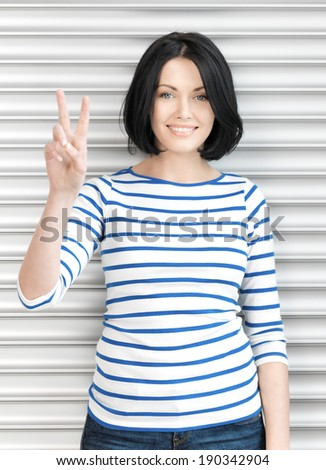 bright picture of lovely teenage girl showing victory sign - stock photo