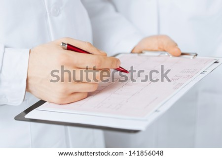 bright picture of male doctor hands holding cardiogram - stock photo