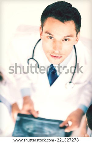 bright picture of male doctor with x-ray - stock photo