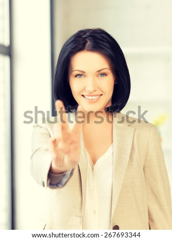 bright picture of young woman showing victory sign - stock photo