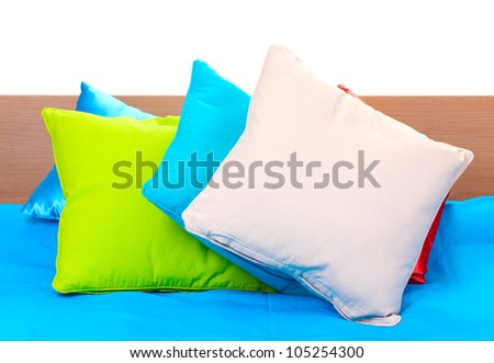 bright pillows on bed on white background - stock photo