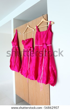 Bright pink bridesmaids dresses hanging up before a wedding. - stock photo